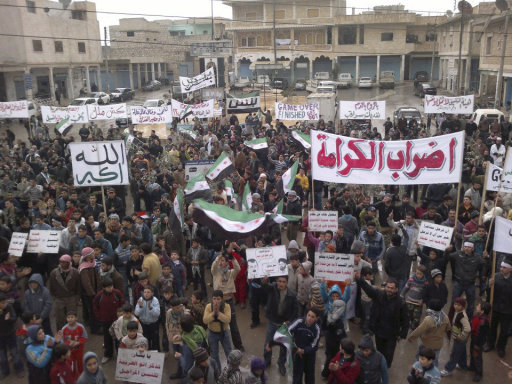 Demonstrators protesting against Syria's President Bashar al-Assad gather during a march through the streets after Friday prayers near Adlb