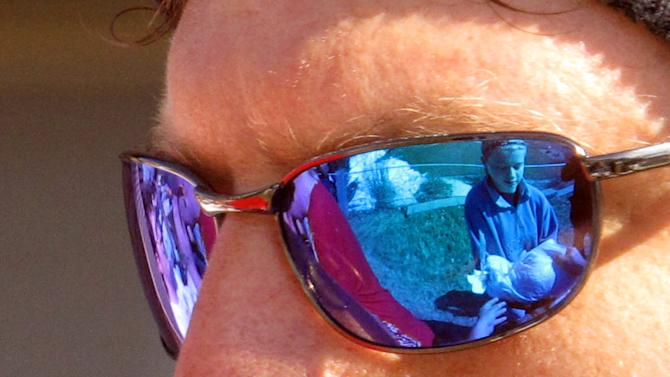 Seventh grade volunteer Brooke Peterson, 13, is reflected in the sunglasses of Fargo, N.D. city employee Jim Mohr as he directs sandbagging operations along the Red River Friday, April 26, 2013, in Fargo. Hundreds of students pitched in, in what has become a nearly-annual sandbag party, to place 100,000 sandbags around Fargo and help protect homes against Red River flooding. (AP Photo/Dave Kolpack)