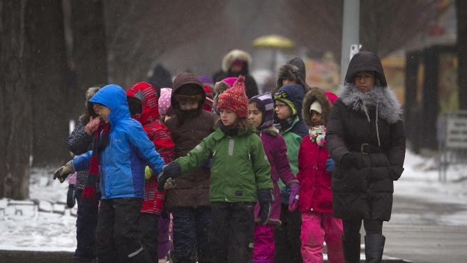 Grade schoolers walk towards Central Park as it snows in the Manhattan borough of New York