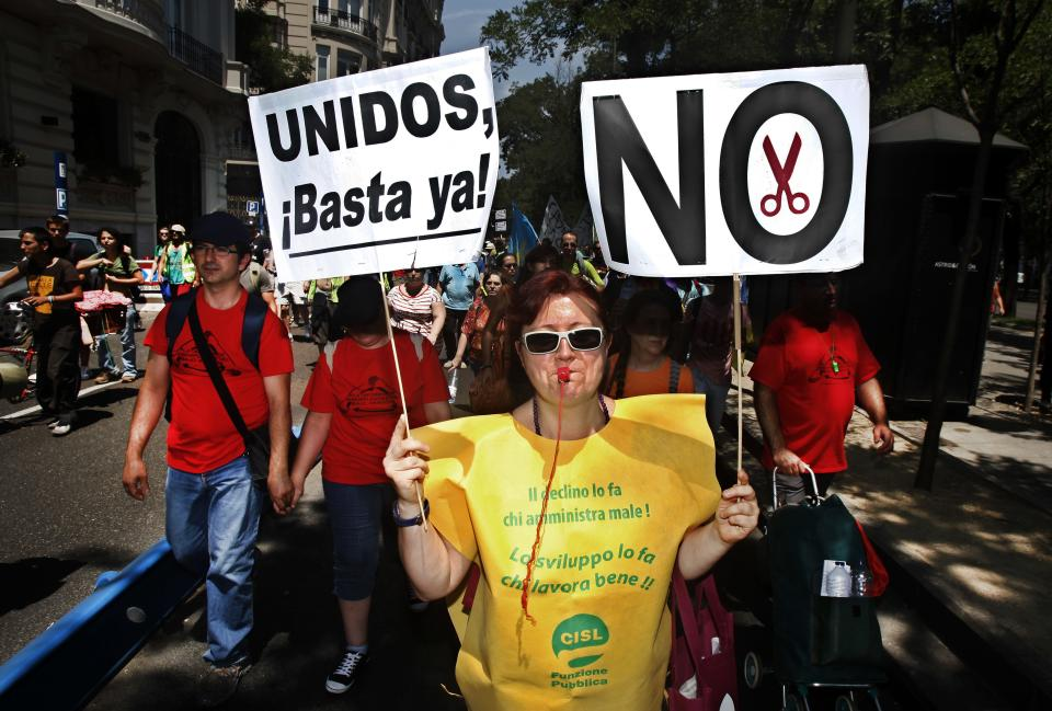 "Protesters carry banners reading ""United, let's stop this now"" as they demonstrate against the country's near 25 percent unemployment rate and stinging austerity measures introduced by the government, in Madrid, Spain, Saturday, July 21, 2012. (AP Photo/Andres Kudacki)"