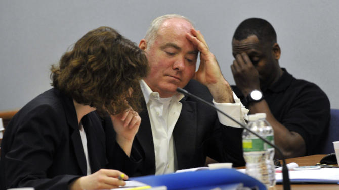 Michael Skakel, center, listens to testimony from his former defense attorney, Michael Sherman during the second day of Skakel's appeal trial at Rockville Superior Court on Wednesday, April 17, 2013 in Rockville, Conn.  Attorney's for Skakel Sherman of having a good time making trips around the country instead of preparing for the case.  Skakel is the 52-year-old nephew of Robert F. Kennedy's widow, Ethel. He's serving 20 years to life in prison for the 1975 golf club bludgeoning of Greenwich neighbor Martha Moxley when they were both 15.  (AP Photo/The Stamford Advocate, Jason Rearick, Pool)