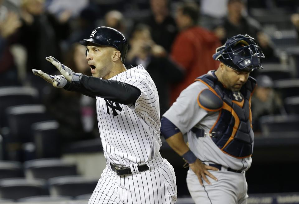 New York Yankees' Raul Ibanez celebrates after hitting a two-run home run in the ninth inning of Game 1 of the American League championship series Saturday, Oct. 13, 2012, in New York. Detroit Tigers catcher Gerald Laird is at rear. (AP Photo/Paul Sancya )