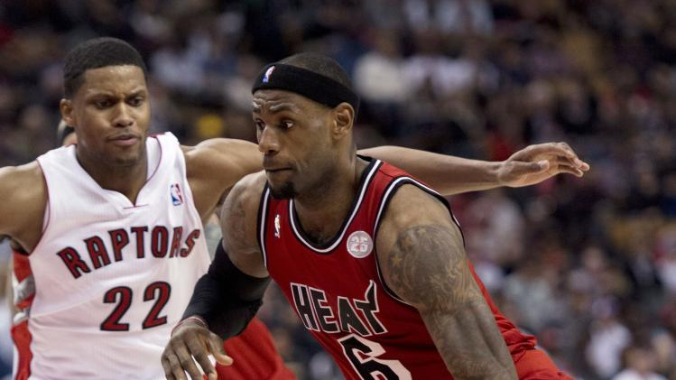 Miami Heat forward LeBron James, right, drives to the hoop against Toronto Raptors forward Rudy Gay (22) during second half NBA basketball action in Toronto Sunday Feb. 3, 2013. (AP Photo/THE CANADIAN PRESS IMAGES,Frank Gunn)