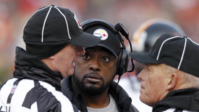 Pittsburgh Steelers head coach Mike Tomlin listens to head linesman Jim Howey (37), left, and side judge Tom Hill (97) in the first quarter of an NFL football game against the Cleveland Browns Sunday, Nov. 25, 2012, in Cleveland. (AP Photo/Ron Schwane)