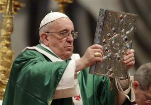 Pope Francis holds the Book of the Gospels as he celebrates a mass in Saint Peter's Basilica at the Vatican