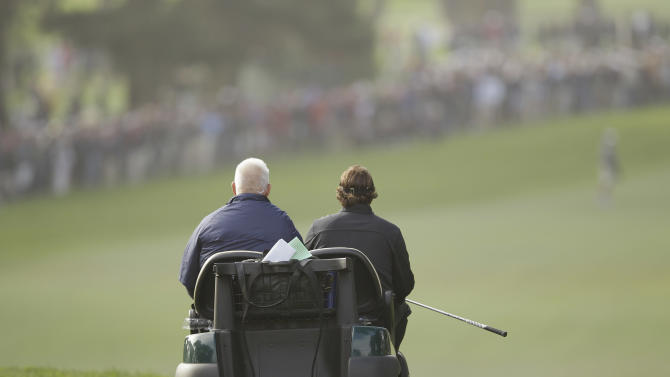 Phil Mickelson gets a ride in a cart after having to take a second tee shot on the ninth hole after losing a ball in a tree during the first round of the U.S. Open Championship golf tournament Thursday, June 14, 2012, at The Olympic Club in San Francisco. (AP Photo/Eric Risberg)