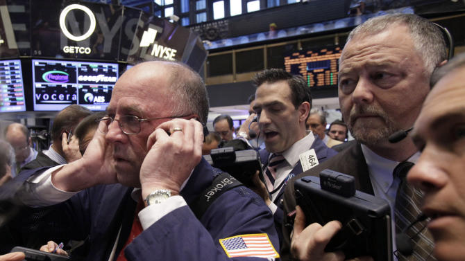 In an April 12, 2012 file photo traders Frederick Reimer, left, Gregory Rowe, center, and Robert Moran, second from right, work on the floor of the New York Stock Exchange. U.S. futures augured a lower open on Wall Street Friday June 8, 2012. Dow Jones industrial futures fell 0.7 percent to 12,316 and S&P 500 futures lost 0.8 percent at 1,299.60.   (AP Photo/Richard Drew)