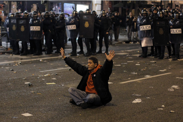 A protestor sits in front of the riot police riot to stop the clashes during a general strike in Madrid, Spain, Wednesday, Nov. 14, 2012. Spain's main trade unions stage a general strike, coinciding w