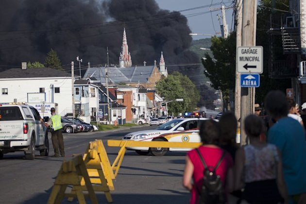 Residents watch rising smoke after a freight train loaded with oil derailed in Lac-Megantic in Canada's Quebec province on June 6, 2013. At least 80 people are missing in the small Canadian town after the accident, a firefighter told AFP