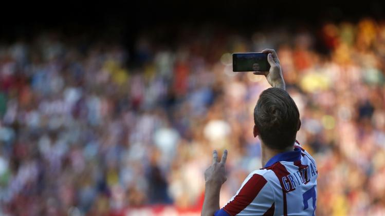 Atletico Madrid's newly signed French soccer player Antoine Griezmann takes a selfie during a media presentation at the Vicente Calderon stadium in Madrid