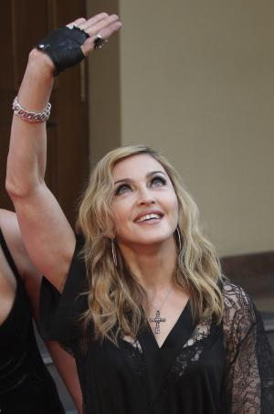 """U.S. singer Madonna greets her fans at the opening of the new fitness club in Moscow, Russia, Monday, Aug. 6, 2012. Madonna has voiced hope that three feminist Russian rockers on trial for performing a """"punk prayer"""" against Vladimir Putin are released soon. The pop star told the AP during her concert tour of Russia that she supports freedom of speech and hopes the judge will show leniency. (AP Photo/Mikhail Metzel)"""