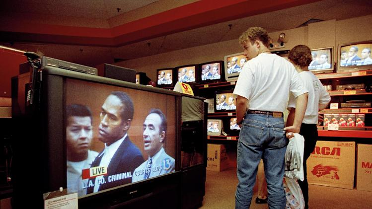 "FILE - In this June 20, 1994 file photo, mall shoppers in Tampa, Fla., watch banks of televisions in an electronics store as the arraignment of O.J. Simpson is televised from Los Angeles. The O.J. Simpson trial was labeled the ""Trial of the century"" and a forerunner of today's interactive media. (AP Photo/Chris O'Meara, File)"
