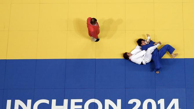South Korea's Kim Seong-yeon competes with Japan's Chizuru Arai in their women's -70kg gold medal judo match during the 17th Asian Games in Incheon