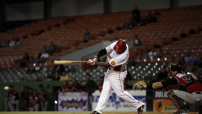 In this Dec. 29, 2012 photo, Criollos of Caguas' Carlos Rivera hits a ball during a baseball game against Leones of Ponce in Caguas, Puerto Rico. On an island where the name of Roberto Clemente is emblazoned on stadiums, streets and schools, the sport of baseball is poised to make a late-inning rally. In the past year, Major League Baseball reported the second-highest number of signings from Puerto Rico since the year 2000. (AP Photo/Ricardo Arduengo)