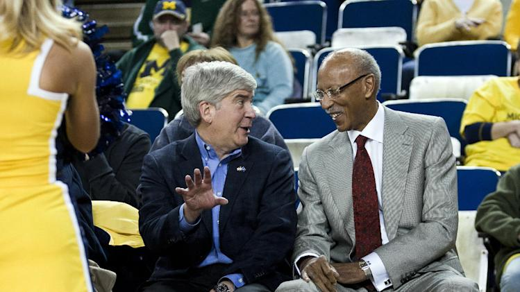 FILE - In this Feb. 23, 2011 file photo Michigan Gov. Rick Snyder, center left, sits with Detroit Mayor Dave Bing at a Michigan basketball game at Crisler Arena in Ann Arbor, Mich. The former NBA great, who transitioned smoothly to owner and founder of a steel supply company, became Mayor of Detroit in 2009.  In basketball and business, he never side-stepped a challenge, but the overwhelming weight of Detroit's financial problems and other troubles have convinced Bing to pass control of the city over to the state. (AP Photo/Tony Ding, File)