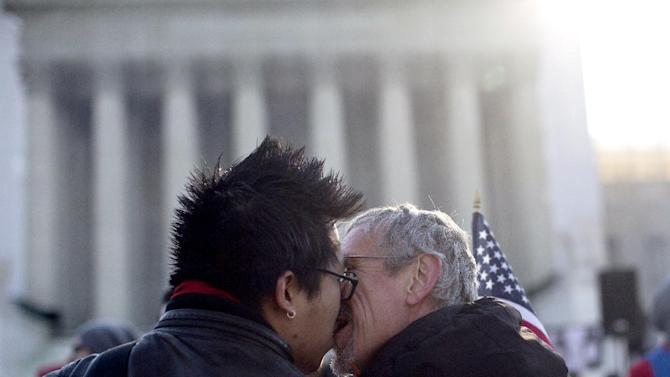 Wyatt Tan, left and Mark Nomadiou, both of New York City, kiss in front of the Supreme Court in Washington, Wednesday, March 27, 2013, prior to the start of a court hearing on the 1996 Defense of Marriage Act (DOMA). In the second of back-to-back gay marriage cases, the Supreme Court is turning to a constitutional challenge to the law that prevents legally married gay Americans from collecting federal benefits generally available to straight married couples.  (AP Photo/Carolyn Kaster)