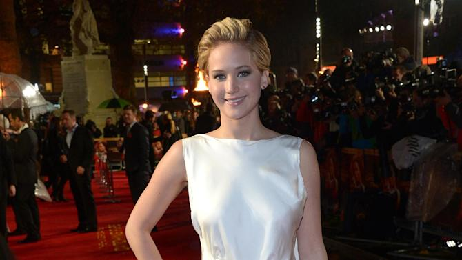 """American actress Jennifer Lawrence poses for photographers as she arrives on the red carpet for the World Premiere of """"The Hunger Games: Catching Fire,"""" on Monday Nov. 11, 2013, in Leicester Square, London. Lawrence will not only star in the upcoming film adaptation of Jeanette Walls' 2005 best-selling memoir """"The Glass Castle,"""" the project will also mark her first time as a producer. A production date for the movie has not yet been set. (Photo by Jon Furniss/Invision/AP)"""