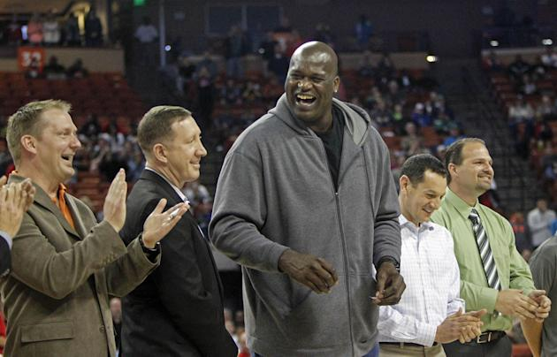 Former NBA star Shaquille O'Neal laughs with his former high school teammates during halftime of the boys' UIL Class 1A Division 1 state basketball final, Saturday, March 8, 2014, in Austin, T