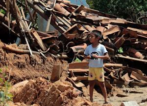 A boy stands next to his house detroyed by tropical …