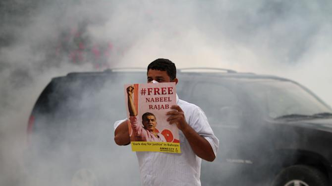 A Bahraini anti-government protester holds a poster as riot police, unseen, fire tear gas outside the home of jailed human rights activist Nabeel Rajab in Bani Jamra, Bahrain, on Saturday, March 23, 2013. Security forces in Bahrain fired tear gas to prevent protesters from reaching the house of Rajab, who is the focus of an international campaign seeking his release.(AP Photo/Hasan Jamali)