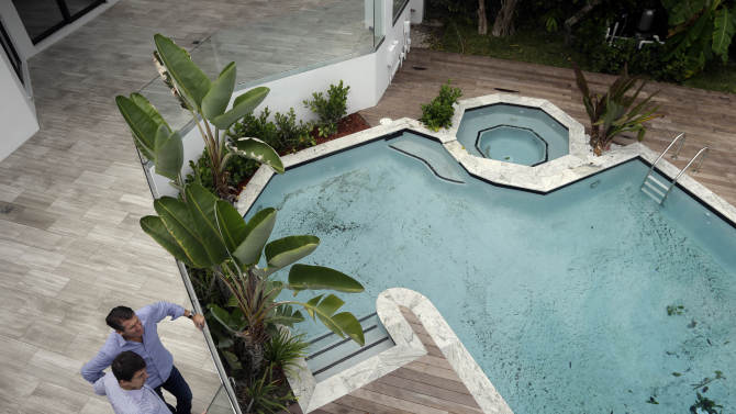 In this Sept. 24, 2014 photo, developer Michael Capponi, left, talks with real estate broker Massimo Nicastro, right, of South Beach Estates, at a waterfront property he renovated, during a viewing for brokers, in Miami Beach, Fla. Standard & Poor's releases S&P/Case-Shiller index of home prices for July on Tuesday, Sept. 30, 2014. (AP Photo/Lynne Sladky)