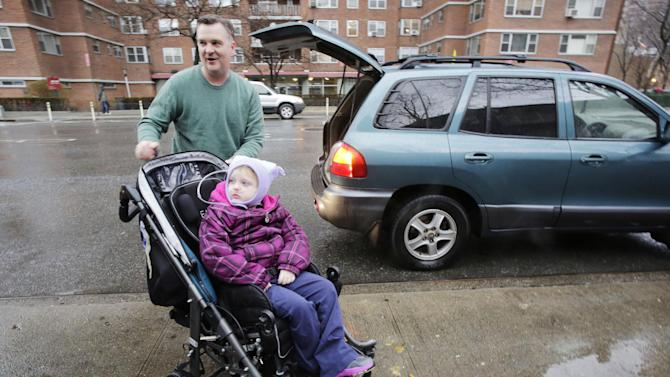 Peter Curry pushes his daughter Maisy, 7, in her wheel chair after driving her to Public School 33, Wednesday, Jan. 16, 2013 in New York. Maisy Curry would normally be driven by school bus, according to her father. More than 8,000 New York City school bus drivers and aides went on strike over job protection Wednesday morning, leaving some 152,000 students, many disabled, trying to find other ways to get to school. (AP Photo/Mark Lennihan)