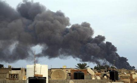 Smoke billows from a factory after an airstrike by forces loyal to former general Haftar, in Benghazi