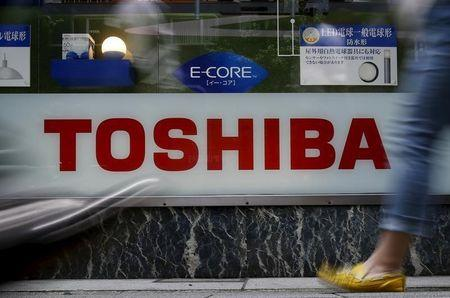 Pedestrians walk past a logo of Toshiba Corp outside an electronics retailer in Tokyo