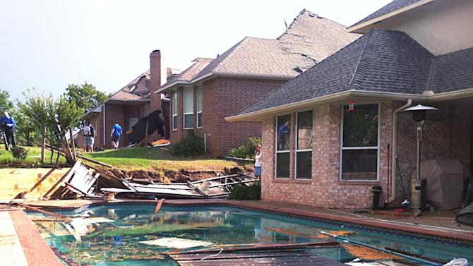 People survey damage from a tornado that hit Edmond, Okla., on Sunday, May 19, 2013. A powerful storm system rumbled through the Plains and upper Midwest on Sunday, spawning tornadoes that damaged roofs and structures near Oklahoma City and kicked up debris in Wichita, Kan. (AP Photo/Sean Murphy)
