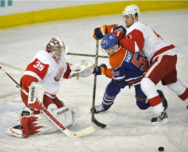 Oilers' Hartikainen is checked by Red Wings' goalie Howard and Kindl during the first period of their NHL hockey game in Edmonton