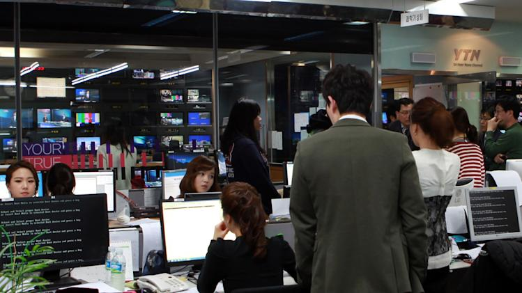 Employees react at the newsroom of the all-news cable channel YTN as the broadcaster's computer network was paralyzed in Seoul, South Korea, Wednesday, March 20, 2013. Computer networks at major South Korean banks and top TV broadcasters crashed en masse Wednesday, paralyzing bank machines across the country and prompting speculation of a cyberattack by North Korea. (AP Photo/Yonhap)  KOREA OUT