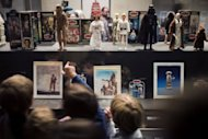 Children look at Star Wars toys displayed during an exhibition at the Arts Decoratifs Museum in Paris. Until March 17, the museum in a wing of the Louvre is hosting epic Jedi battles, stormtroopers on the hunt for droids and grooving aliens at the planet Tatooine&#39;s Mos Eisley Cantina