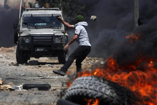 A Palestinian protester throws stones at Israeli security forces during clashes at a protest against the nearby Jewish settlement of Kdumim near Nablus