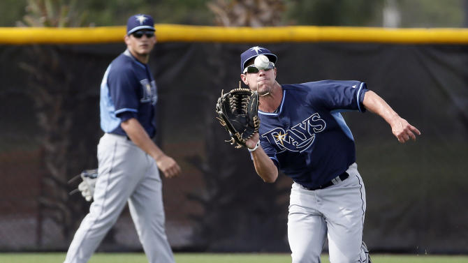 Tampa Bay Rays' Boog Powell reaches out for a fly ball as Mikie Mahtook, rear, watches during fly ball drills at baseball spring training in Port Charlotte Fla., Monday March 2, 2015. (AP Photo/Tony Gutierrez)