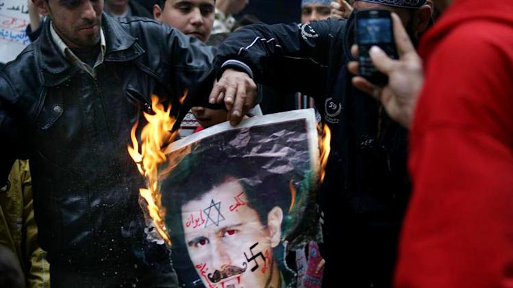 "In this Monday March 25, 2013, citizen journalism image provided by Aleppo Media Center AMC which has been authenticated based on its contents and other AP reporting, anti-Syrian regime protesters burn a portrait for Syrian President Bashar Assad during a protest, in Aleppo, Syria. Syrian activists say government forces have seized control of a neighborhood in the central city of Homs that is a symbol of opposition to President Bashar Assad's regime. The Arabic on the poster reads, the dog of Iran, devil's party (Hezbollah)."" (AP Photo/Aleppo Media Center, AMC)"