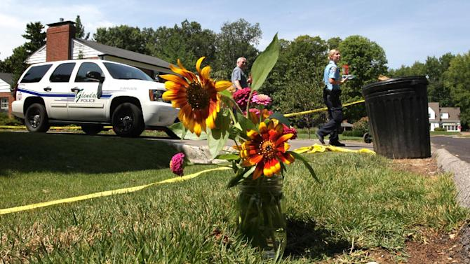 Flowers are left for members of the Murch family in front of their home in Glendale, Mo., on Tuesday, July 31, 2012. A major case squad probing the shooting deaths of suburban St. Louis mother Catherine Murch and her two children unleashed more than 20 investigators Tuesday, but authorities who originally viewed the case as a murder-suicide said it was too early to draw any conclusions. (AP Photo/St. Louis Post-Dispatch, Robert Cohen)  EDWARDSVILLE INTELLIGENCER OUT; THE ALTON TELEGRAPH OUT
