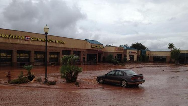 This photo released by the St. George Police Department shows a  flooded parking lot after a dike broke and sent floodwaters through the town of Santa Clara, Utah, Tuesday, Sept. 11, 2012. Officials in Santa Clara say they're inspecting whether people can return to about 60 homes and 15 businesses that were evacuated after a dike broke and sent floodwaters through town. City Parks and Recreation Director Brad Hays said a retention pond fed by the Tuacahn Wash filled up after heavy rains Tuesday morning. Authorities ordered homes and businesses below the pond to evacuate about noon, and the dike broke about 45 minutes later. No injuries have been reported from the flooding. (AP Photo/St. George Police Department)