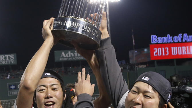 Boston Red Sox relief pitcher Koji Uehara, left, holds the championship trophy with teammate Junichi Tazawa after defeating the St. Louis Cardinals in Game 6 of baseball's World Series, Wednesday, Oct. 30, 2013, in Boston. The Red Sox won 6-1 to win the series. (AP Photo/Elise Amendola)
