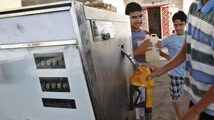 A Palestinian employee fills a container with Israeli diesel at gas station in Gaza City, Thursday, June 27, 2013. An Egyptian security crackdown has severely disrupted smuggling to the neighboring Gaza Strip, causing a fuel shortage, doubling the price of building materials and shutting down some construction sites in the Hamas-ruled territory. (AP Photo/Adel Hana)
