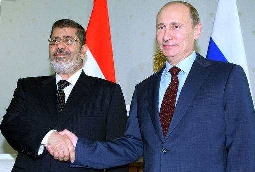 "Russia's President Vladimir Putin (R) shakes hands with his Egyptian counterpart Mohamed Morsi during their meeting in the Black Sea resort of Sochi, on April 19, 2013. Russia and Egypt called for a ceasefire in Syria ""as quickly as possible"", Putin said Friday, after a meeting with Morsi"