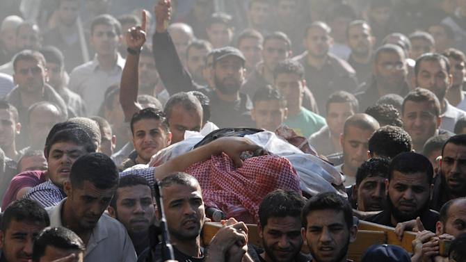 Palestinian mourners carry the body of Hamas' top military commander Ahmed Jabari, killed in an Israeli strike on Wednesday, during his funeral in Gaza City, Thursday, Nov. 15, 2012. Israel barraged the Gaza Strip with airstrikes and shelling Wednesday and killed the Hamas military chief in a targeted strike, launching a campaign aimed at stopping rocket attacks from Islamic militants. The assault killed 10 other Palestinians, including two children and seven militants. On Thursday, militant rockets fired into Israel killed three Israelis, raising the likelihood of a further escalation. (AP Photo/Hatem Moussa)