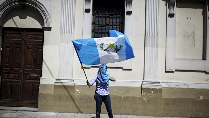 A protester waves a Guatemalan flag outside the Guatemalan Congress during a meeting of an investigative commission in Guatemala City