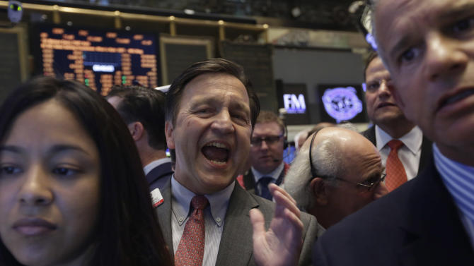 Specialist Thomas Facchine, center, calls out opening prices during the IPO of Mexican airline Volaris, on the floor of the New York Stock Exchange, Wednesday, Sept. 18, 2013.  Stocks were little changed in early trading Wednesday as investors wait to hear from the Federal Reserve on the fate of the central bank's bond-buying program. (AP Photo/Richard Drew)