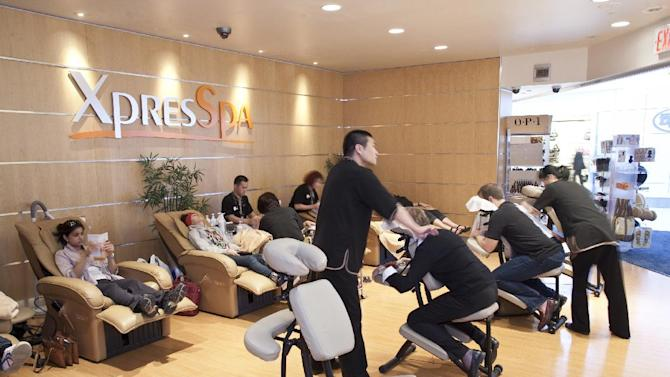 This undated image provided by XpresSpa shows the customers receiving massages and other treatments at the company's spa at John F. Kennedy International Airport in New York. XpresSpa offers manicures, pedicures, massages, haircuts and other treatments at 46 airport locations and sells gift cards for their services that can be given as holiday gifts for travelers. (AP Photo/XpresSpa, Lance Davies)
