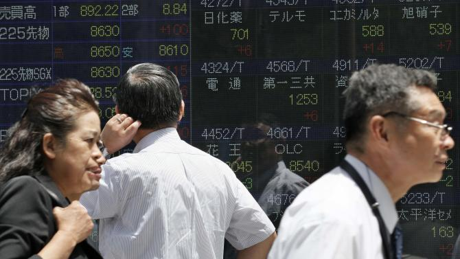 A man checks share prices as others walk by the electronic stock board of a securities firm in Tokyo Thursday, June 7, 2012. Asian stock markets rose Thursday, boosted by hopes that Europe is preparing to take action to tackle the region's financial crisis and comments from a Fed policymaker about possible support for the U.S. economy. (AP Photo/Koji Sasahara)