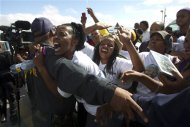 A woman hugs a police officer as the funeral cortege of former South African President Nelson Mandela passes through Mthatha, December 14, 2013. REUTERS/Rogan Ward