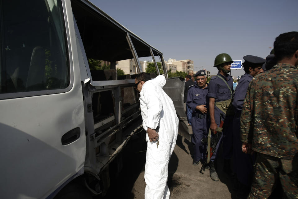 A Forensic expert, center, inspects a damaged bus after a bomb attack in Sanaa, Yemen, Sunday, Aug. 25, 2013. A powerful blast ripped through the bus carrying air force personnel down a main street in Yemen's capital on Sunday, causing at least a score of casualties, officials said. (AP Photo/Hani Mohammed)
