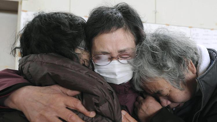 Women wail together after hearing the death of family members at an evacuation center in Kesennuma in Miyagi prefecture (state) Tuesday, March 15, 2011, after Friday's massive earthquake and tsunami. (AP Photo/Kyodo News) JAPAN OUT, MANDATORY CREDIT, NO LICENSING IN CHINA, HONG  KONG, JAPAN, SOUTH KOREA AND FRANCE
