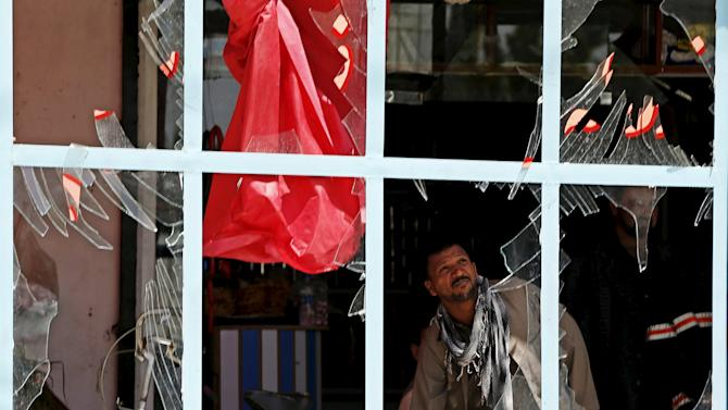 An Afghan man removes broken glass from his shop after a suicide attack in Kabul