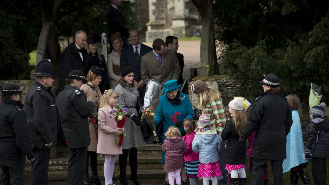Britain's Queen Elizabeth II, center, receives flowers from children after attending the British royal family's traditional Christmas Day church service in Sandringham, England, Tuesday, Dec. 25, 2012.  (AP Photo/Matt Dunham)